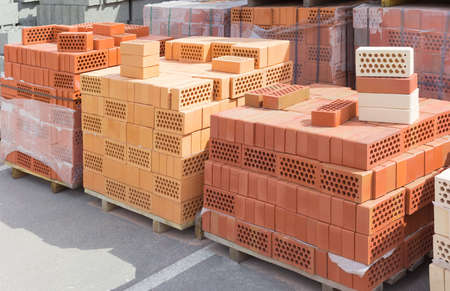 Several pallets of common perforated bricks different colors with round holes on the background other pallets with bricks on warehouse