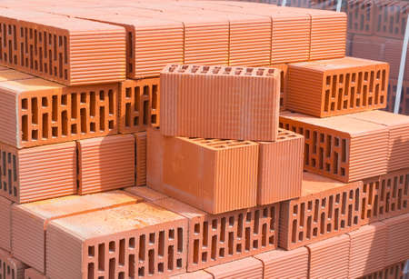 Wall blocks made from red porous ceramics with rectangular holes on a pallet