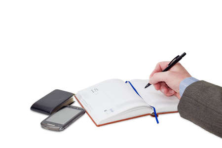 appointment book: Male hand with pen over business diary with blue page-marker ribbon, wallet for business cards and mobile phone on a light background Stock Photo