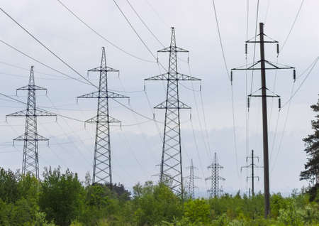 power line tower: One overhead power line with reinforced concrete poles and several overhead power lines with steel lattice structures transmission tower against the backdrop of an overcast sky Stock Photo
