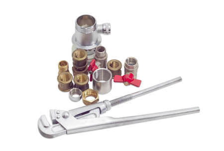 adapters: Plumber wrench and several brass and steel pipe couplings, adapters, nuts, ball valves and trap on a light background Stock Photo