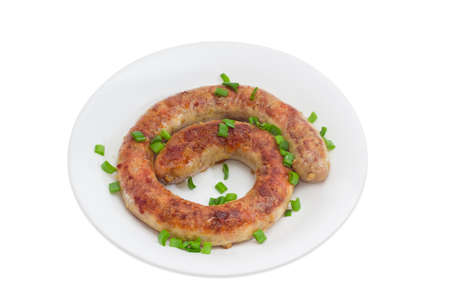 casings: Fried homemade sausage sprinkled with chopped green onions on a white dish Stock Photo