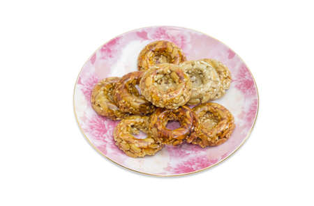 gozinaki: Kozinaki in the form of rings made from syrup, sunflower and sesame seeds on a pink saucer on a light background
