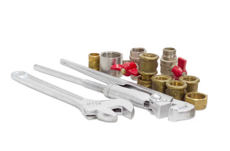 water sanitation: Plumber wrench, adjustable wrench with silvery coating and several different steel and brass plumbing components on a light background