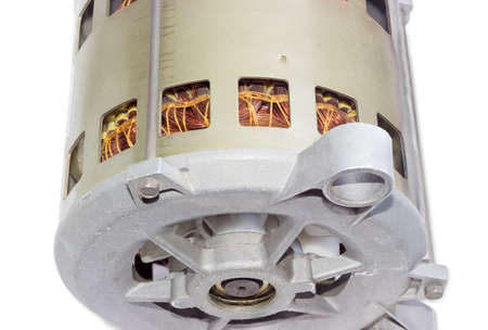 windings: Fragment of alternating current motor with ventilation holes in the housing, through which can be seen windings, closeup on a light background