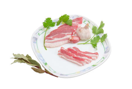 uncooked bacon: Several slices of uncooked streaky pork belly bacon, garlic and sprigs of cilantro on a dish and laurel branch on a light background