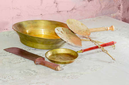 outmoded: Some subjects of a older kitchen utensils consisting of two various copper frying pans and slotted spoons, large kitchen knife on table with old tablecloth against background of the brickwork