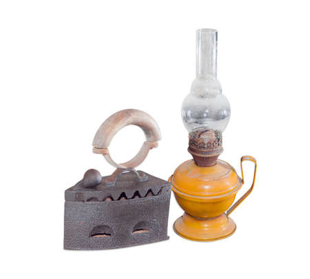 the outmoded: Old charcoal iron and old flat wick kerosene lamp on a light background