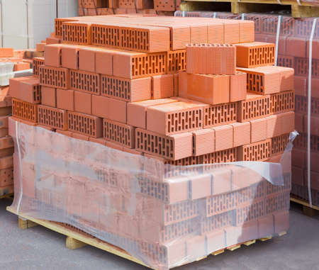Wall blocks made from red porous ceramics with rectangular holes on a pallet on warehouse Reklamní fotografie