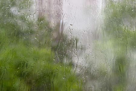 Antecedentes de una arroyos y gotas de agua sobre el cristal de la ventana y el follaje borrosa a través del cristal durante un aguacero