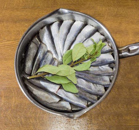 steel pan: Cut and prepared for cooking raw baltic herring and a sprig of bay leaf in a stainless steel pan on a wooden table Foto de archivo