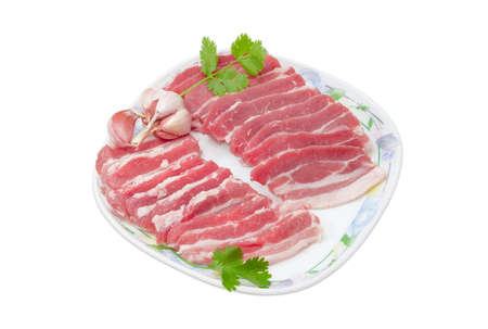 uncooked bacon: Several slices of uncooked streaky pork belly bacon, garlic and sprigs of cilantro on a dish on a light background