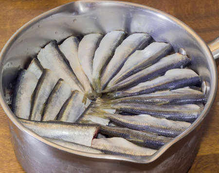 steel pan: Cut and prepared for cooking raw baltic herring in a stainless steel pan on a wooden table closeup