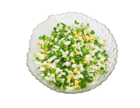 green onions: Top view to spring salad with chopped green onions and chopped boiled eggs in a glass salad bowl on a light background Stock Photo