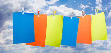 colored paper: Blank sheets of colored paper, fixed a plastic clothespins with colored inserts on clothesline against the sky with clouds