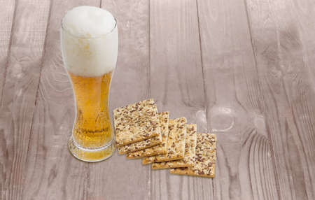 flax seeds: Beer glass with lager beer and savory biscuits with sesame seeds, flax seeds and sunflower on a wooden surface Stock Photo