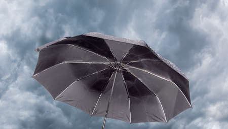 brolly: Open male black folding umbrella against the background of sky with thunder clouds