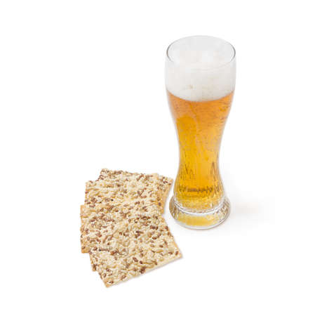 flax seeds: Beer glass with lager beer and savory biscuits with sesame seeds, flax seeds and sunflower on a light background Stock Photo