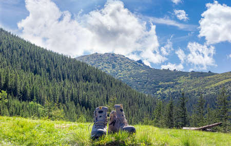 hillwalking: Pair of leather light brown trekking shoes in a clearing in the grass against the backdrop of mountain slopes covered with fir forest and sky with clouds Stock Photo