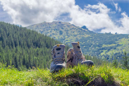 watertight: Pair of leather light brown trekking boots in the grass on a blurred background of forested mountains and sky