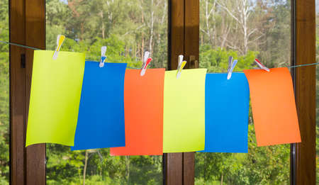 colored paper: Blank sheets of colored paper, fixed a plastic clothespins with colored inserts on clothesline on a blurred background of the window and the trees