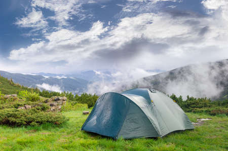 hillwalking: Green tunnel hiking tent after the storm on the background of a mountains and sky with swirling clouds