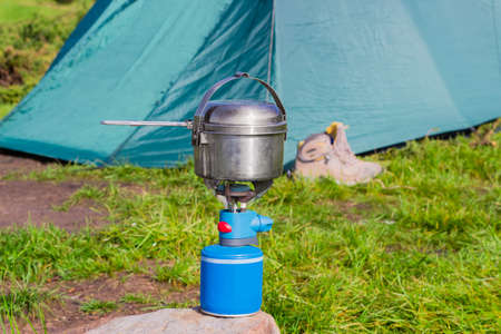 stainless steel pot: Blue gas cartridge camping stove and small stainless steel pot on a stone on a background of the tent during cooking Stock Photo