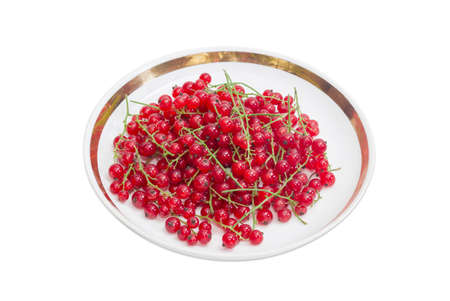 redcurrant: Berries of fresh redcurrant on a saucer on a light background Stock Photo