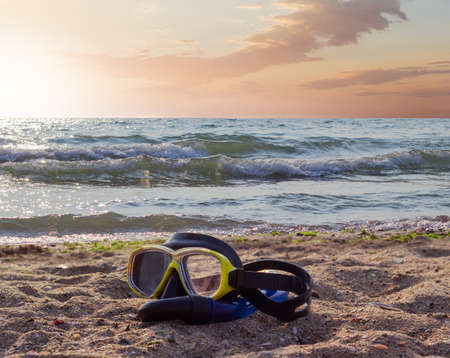freediving: Diving mask with snorkel on a sandy beach against the sea and sky in the morning