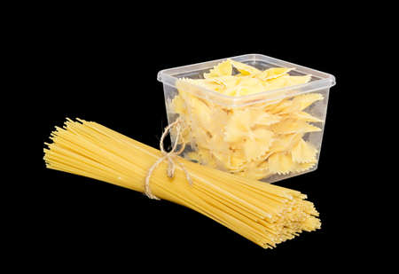 durum: Uncooked bow-tie pasta in transparent plastic tray and bundle of dried long pasta on a dark background