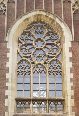 gothic revival style: Window of a gothic cathedral with segments by stone mullions and tracery in Lviv Stock Photo