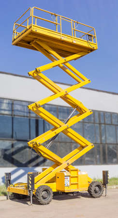 propelled: Mobile aerial work platform - yellow scissor hydraulic self propelled lift against the backdrop of an industrial building