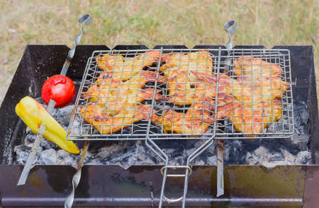 charcoal grill: Grilled chicken wings on a cooking grid over barbecue charcoal grill outdoors