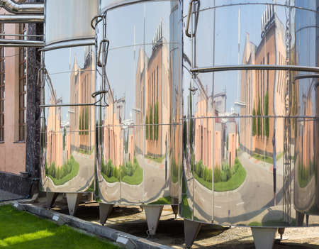 oenology: Several stainless steel vessels used for the production of wine, in which are reflected the surrounding buildings in the modern winery