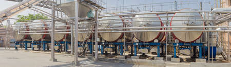 oenology: Panorama of a several stainless steel vessels and pipework and other equipment used for the production of wine in modern winery Stock Photo