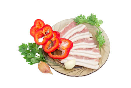uncooked bacon: Uncooked slices of streaky pork belly bacon on glass saucer, sliced bell pepper, sprigs parsley and coriander, garlic cloves on a light background