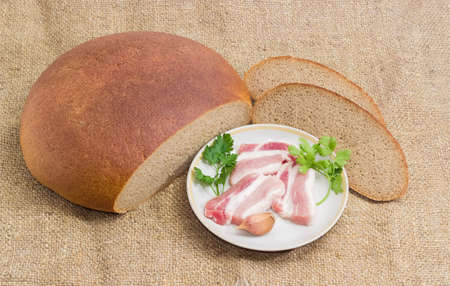 uncooked bacon: Uncooked slices of streaky pork belly bacon, sprigs parsley and coriander and garlic on saucer, partly sliced brown wheat and rye hearth bread on a sackcloth Stock Photo