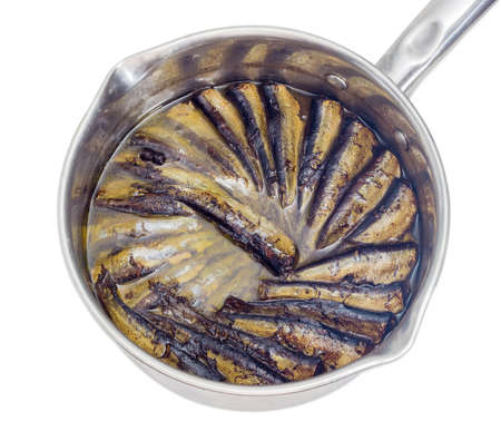 vegetable oil: Smoked sprats cooked in vegetable oil in a stainless steel saucepan closeup on a light background
