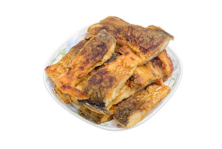 White dish, filled with pieces of fried carp on a light background