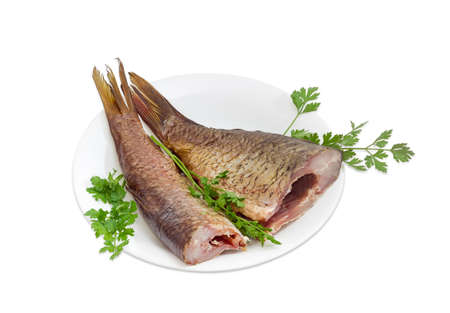 grass carp: Two hot smoked grass carp and sprigs of a parsley on a white dish on a light background