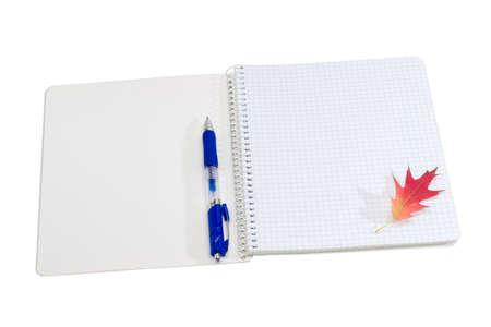 ball pens stationery: cuaderno de papel abierto con hoja espiral vinculante y vacía de un papel cuadriculado, bolígrafo azul y rojo hoja de otoño de un roble sobre un fondo claro
