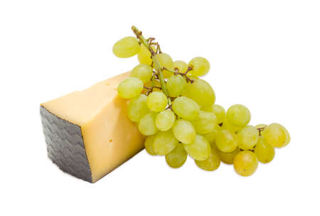 hard cheese: Piece of a hard cheese and cluster of a white table grapes on a light background
