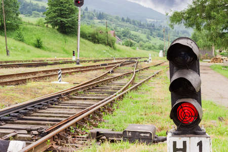 forest railroad: Railroad tracks and other railway equipment with traffic light glows red on the foreground on the provincial railway station in the Carpathians at summer evening Stock Photo
