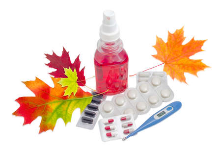 Blue electronic medical thermometer, throat spray, several packaging of medications and autumn leaves on a light background
