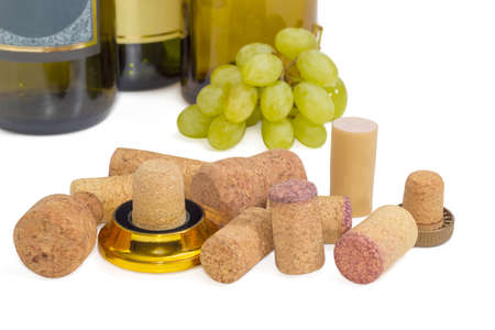 Several different traditional and synthetic wine corks on the background bottles of wine and cluster of white grapes closeup on a light background