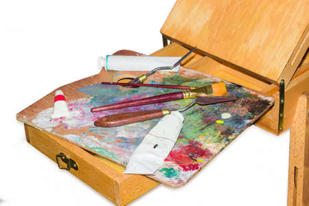 Fragment of wooden easel with paints, brushes and painting knifes on the palette closeup on a light background