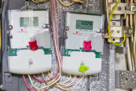 electricity meter: Two domestic digital solid-state electricity meter in transparent plastic case with variable-rate meters, mounted in distribution board