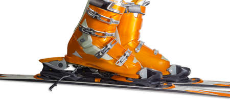 Orange alpine ski boots with four buckles in ski binding. One shoe is completely fastened to the ski, a second just put in binding. Stock Photo