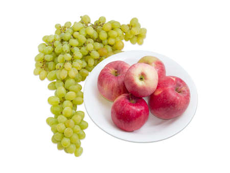 Several red apples on white dish and cluster of white table grapes beside on a light background