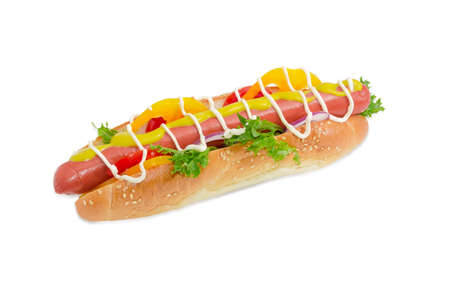 Hot dog with frankfurter, mustard, mayonnaise and vegetables in bun with sesame seeds on a light background